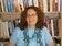 Picture of presenter: Deborah in blue smiles surrounded by her impressive library