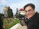 Picture of presenter: Craig holds a camera while at the gardens surrounding the Shrine of the Bab